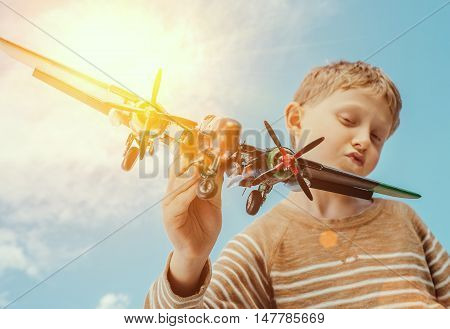 Boy play with toy plane on the blue sky background