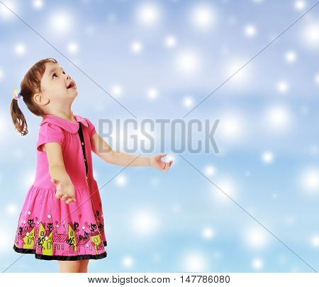 Adorable little girl with pigtails on the head , in a pink dress. The girl was looking at the top turned sideways to the camera.On new year or Christmas blue background with white big stars.