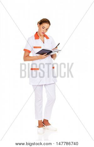 Young focus female doctor or nurse makes notes