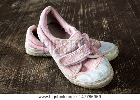 A pair of old pink sneakers on wooden background. Close up.