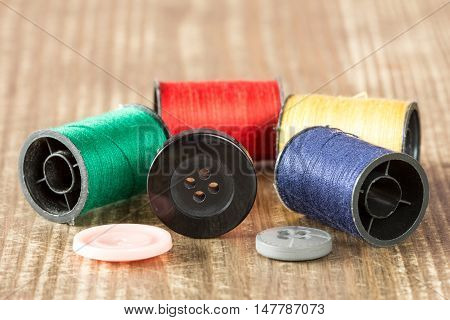 Spools of colored thread and buttons on wooden background.