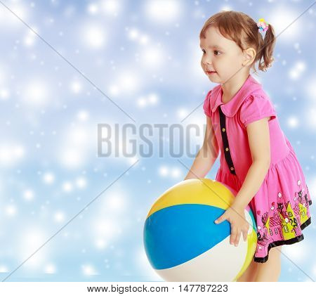 Beautiful little girl in a pink dress throwing a big striped ball. Turned sideways. Close-up.On new year or Christmas blue background with white big stars.