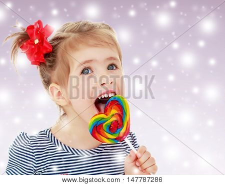 Cute little blonde girl with a red bow on her head, with pleasure licking colorful candy on a stick. Visible language which was painted in a candy color. Close-up.On new year purple background