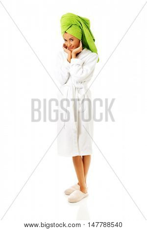 Woman in bathrobe touching face
