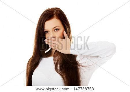 Young woman covering mouth because of shame