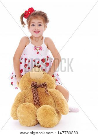 Cute little girl in a light summer dress that hugs a Teddy bear - Isolated on white background
