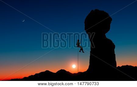 A climber descends in solitary abseiling from a rocky peak after climbing the mountain at sunset