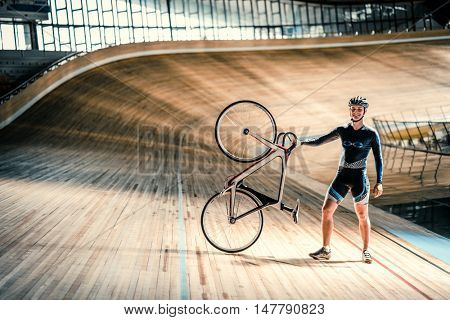 Athlete with a bicycle on a sports track