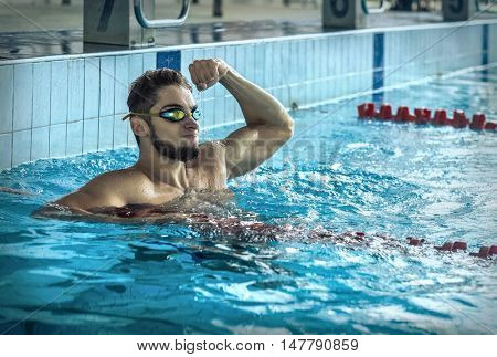 Swimmer man. Portrait of swimming athlete with glasses after training in waterpool.