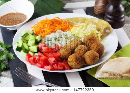 falafel plate on top to garnish, carrot, cabbage, onion, cucumbers, tomatoes, still life dish restaurant
