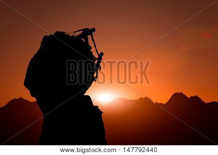 Team Of Climbers Help To Conquer The Summit At Sunset