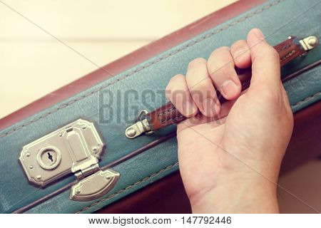 hand holds the handle of an old leather suitcase top view / comfortable for traveling