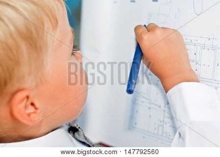 Baby businessman studying drawings on the tablet. Education and business