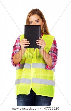 Female builder in a helmet and a vest with a notebook