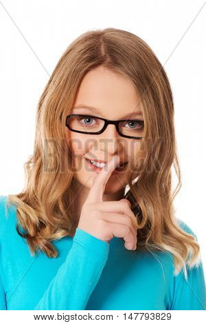 Teenage woman with finger on lips