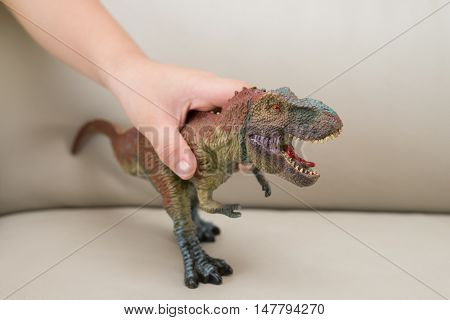 kids hand catching a tyrannosaurus toy on a sofa at home