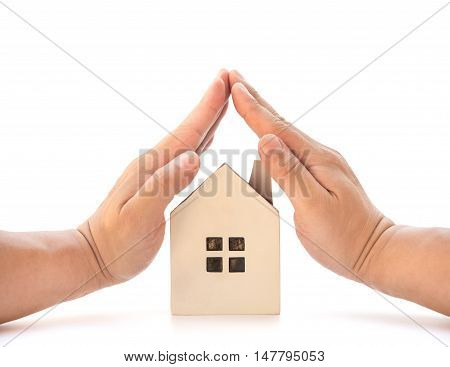 hands covering a small family house home insurance concept or representing home ownership