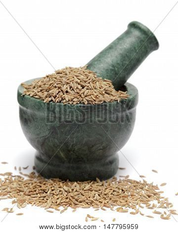 Organic Cumin seed (Cuminum cyminum) on marble pestle and over white background.