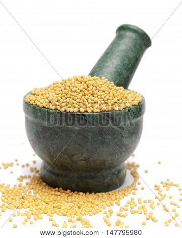 Organic Yellow Mustard (Brassica alba) on marble pestle and over white background.