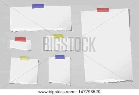 Pieces of ripped white note, notebook paper are stuck with sticky tape on gray background.