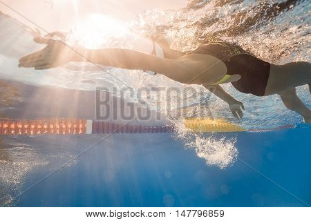 Sunlight falls on girl who swims in back crawl style underwater in the swim pool outdoors. She wears a black-gray swimsuit, a white swim cap and swim glasses. Splashes are around her body. Horizontal.
