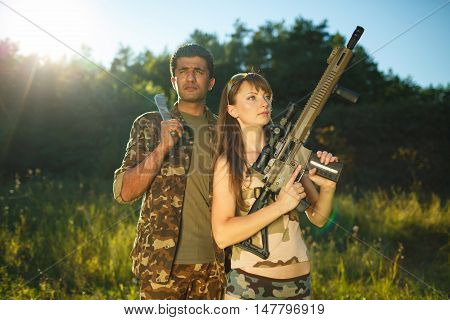 White young girl and an Arab man in camouflage with a weapon in the hands of outdoors