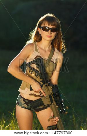 Young beautiful girl in camouflage with a shotgun in an outdoor
