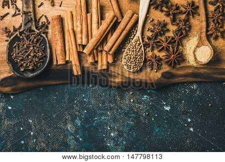 Winter warming spices for baking or cooking mulled wine. Cinnamon, carnation cloves, anise, cardamom and brown sugar on wooden board over old dark blue painted plywood background, top view, copy space