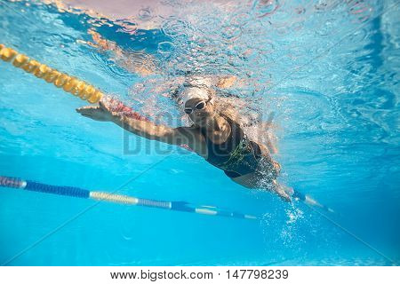 Beautiful girl swims underwater in the swimming pool outdoors. She wears a black-gray swimsuit with patterns, white swim cap and swim glasses. Sunlight falls from above. Splashes are around her body.
