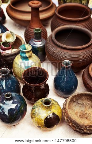 Lots of handmade earthenware - ceramic pots and vases at pottery shop. Colorful clayware background