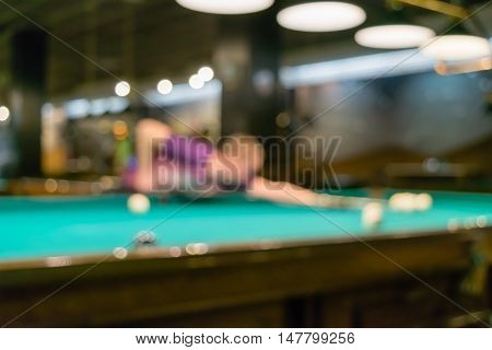 Young man intently looking at the billiard ball. Low depth of focus.