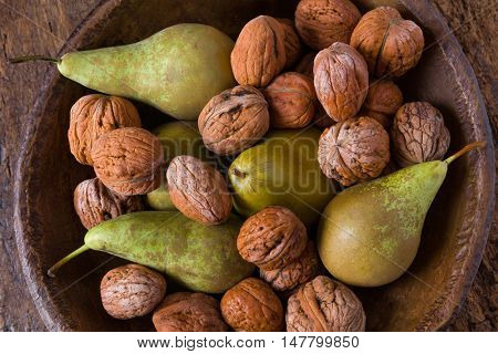 Autumn still life of fall leaves and walnuts on a grunge wooden background