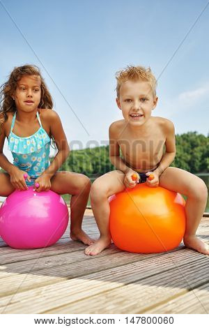 Two happy children sitting on a spacehooper at a lake in summer