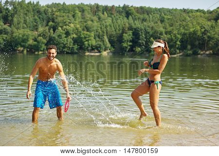 Happy couple splashes and sprays each other with water