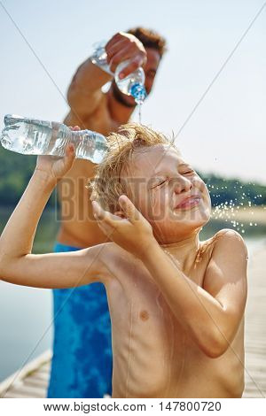 Father sprays son on the face with water at the lake on ther summer holidays