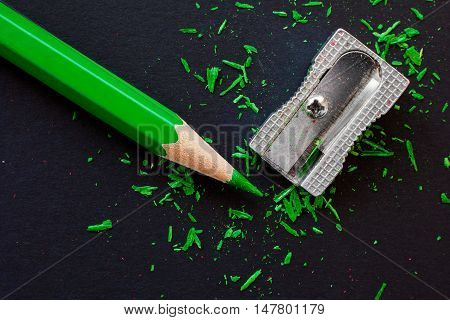 green wooden pencil and sharpeners on black