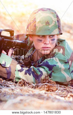Military woman in camo holding gun