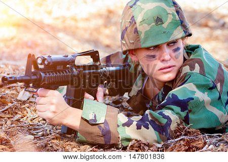 Army woman holding machine gun