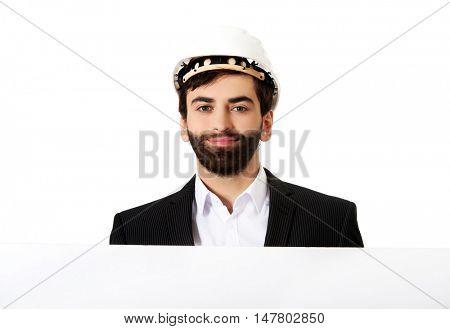 Handsome engineer in helmet holding empty banner.