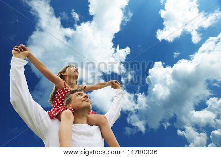 Father and daughter against sky