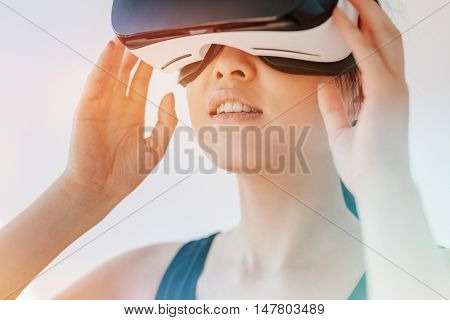 Close up shot of asian woman using the virtual reality headset and looking away. Female wearing VR goggles against grey background.