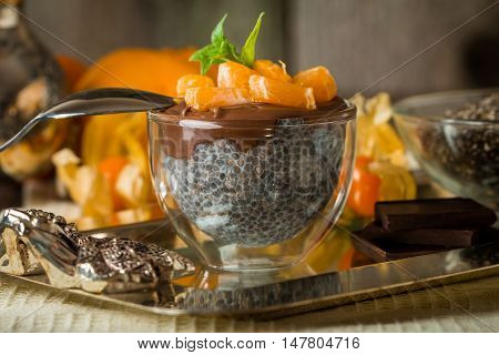 Chocolate chia seed pudding in glass bowl with chia seeds, chocolate mandarin and mint  on top on metal tray over wooden background