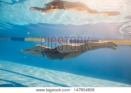 Good swimmer swims in crawl style underwater in the swim pool outdoors. She wears black-gray swimsuit, white swim cap and swim glasses. Sunlight falls from above. Her body reflected in water surface.
