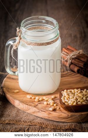 cedar milk in a glass jar and pine nuts in bowl on wooden background