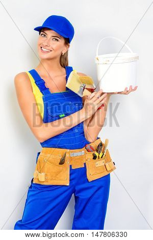 Happy smiling woman painter in overalls holding brushes. Construction worker. Occupation.