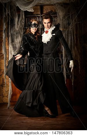 Gorgeous couple of vampires dressed in medieval clothing dancing in the old abandoned castle. Halloween. Carnival.