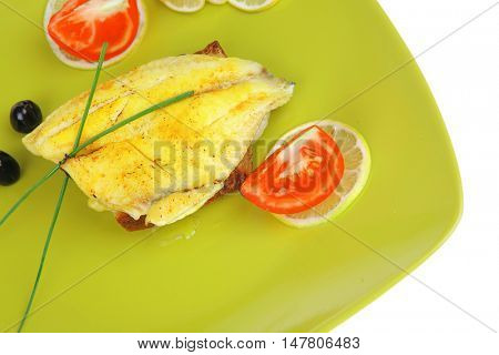 roast sea sole fish fillet served on bread with tomatoes,olives and chives on green plate isolated over white background
