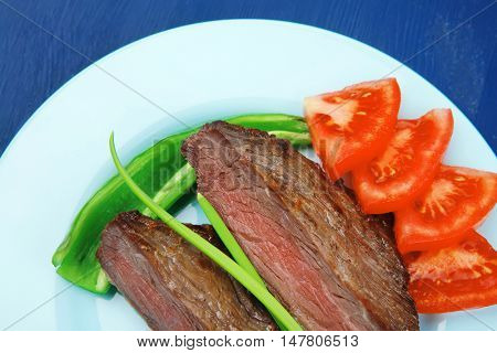 meat savory : grilled beef fillet mignon served on blue plate over blue wooden table with chili pepper and tomatoes