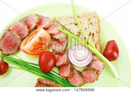 meat savory : roasted bbq meat served on green plate with tomatoes and sprouts isolated on white background