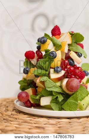 Delicious Christmas tree made of freash organic fruit and berries: raspberry kiwi apple grapes blueberry strawberry mint. Christmas dessert or snack for family celebrations. Season holidays.